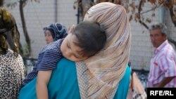 Женщина-узбечка со своим ребенком. Ош, 27 июня 2010 года.