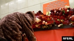 People lay flowers and candles at the Lubyanka subway station