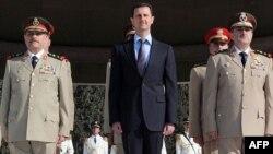 Սիրիայի նախագահ Բաշար ալ-Ասադը, պաշտպանության նախարար Դավուդ Ռաջան (աջից) եւ զինված ուժերի գլխավոր շտաբի պետ Ֆահիդ ալ-Ջասիմ ալ-Ֆրեյջը (ձախից), արխիվային լուսանկար