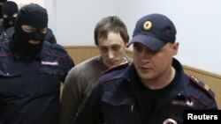 Bolshoi Theater dancer Pavel Dmitrichenko (center) is escorted to a court session in Moscow on October 16.