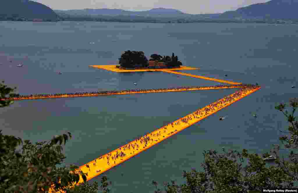 People walk on The Floating Piers