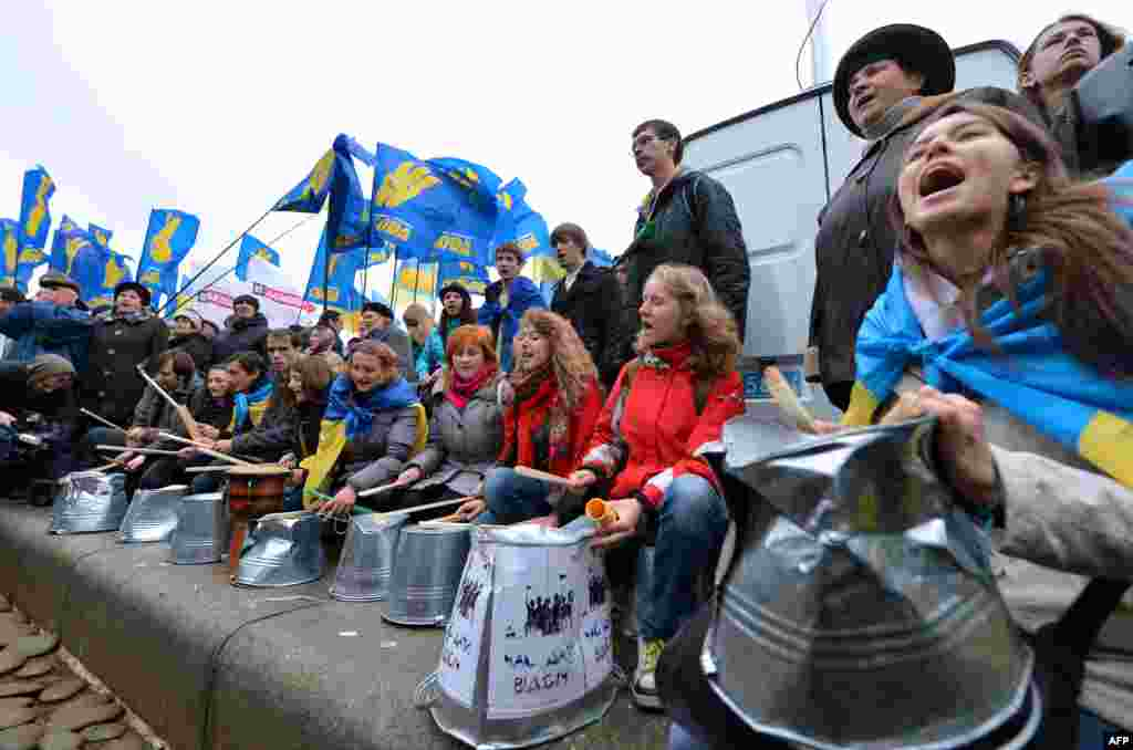 Protesters shout slogans and use buckets as drums.