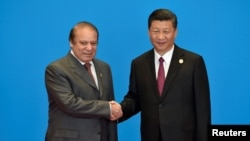 Pakistani Prime Minister Nawaz Sharif (L) shakes hands with Chinese President Xi Jinping during the welcome ceremony for the Belt and Road Forum in May.