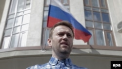 Anticorruption blogger and opposition leader Aleksei Navalny speaks to journalists in front of the Lyublinsky district court in Moscow on April 23.