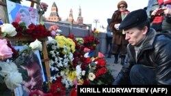 Мужчина возлагает цветы к месту, где в феврале 2015 года был убит российский оппозиционер Борис Немцов. 27 февраля 2017 года.