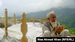Eighty-year-old Gul Shirin prays next to the fresh graves of 13 family members who died in flooding in Swat Valley in August.