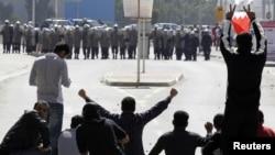Bahreýnli ýaşlar polisiýanyň öňünde demonstrasiýa geçirýärler, Manama, 14-nji fewral 2011-nji ýyl.