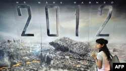"""Девушка стоит рядом с постером к фильму """"2012"""". Иллюстративное фото."""