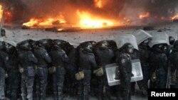 """Бойцы спецподразделения украинской милиции """"Беркут"""" стоят напротив подожженных протестующими автопокрышек. Киев, 22 января 2014 года."""
