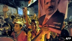 Supporters of Egypt's deposed president, Muhamad Morsi, hold up his image during a protest in the Mediterranean city of Alexandria late on August 5.