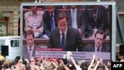 """Лондондерри тұрғындары үлкен телеэкраннан британ премьер-министрі Дэвид Кэмеронның """"қанды жексенбі"""" оқиғасы үшін кешірім сұраған сөзін тыңдап тұр. Солтүстік Ирландия, 15 маусым 2010 ж."""