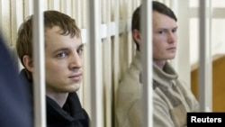 Opposition activists Zmitser Dashkevich (left) and Eduard Lobau sit inside a guarded cage during a court hearing in Minsk on March 24.