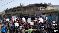 "Antigovernment protesters, some holding signs reading ""We only love freedom,"" march in northeastern Syria on April 1."