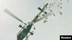 Военный вертолет сбрасывает листовки с требованием покинуть площадь.