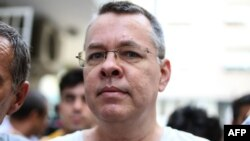 U.S. pastor Andrew Craig Brunson is escorted by Turkish plainclothes police officers to his house in Izmir on July 25.