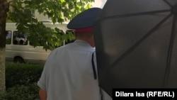 Неизвестный с зонтом пытается препятствовать журналисту Азаттыка Диларе Исе проводить съемку задержаний полицией граждан. Шымкент, 10 июня 2019 года.