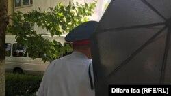 Белгісіз біреу Азаттық тілшісі Динара Исаның камерасын қолшатырмен жауып тұр. Шымкент, 10 маусым 2019 жыл.