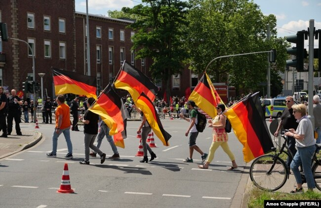 A group of demonstrators opposed to the unveiling carrying German flags. The Lenin monument is visible, covered in a red sheet, in the background.