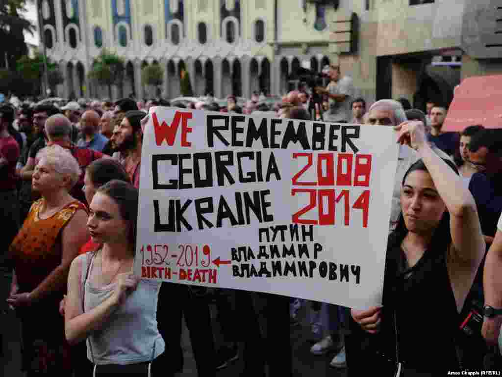 Activists' signs are referring to Georgia's 2008 conflict with Russian forces over the breakaway regions of South Ossetia and Abkhazia, when Russian tanks drove near Tbilisi, as well as the ongoing conflict in eastern Ukraine. Among the protesters' demands is the resignation of the country's interior minister, Giorgi Gakharia.