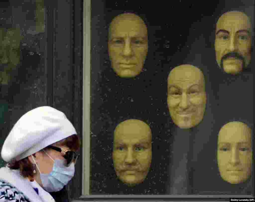 A woman wearing a mask to protect against the coronavirus walks past model faces displayed in a window of a wax museum in St. Petersburg, Russia. (AP/Dmitri Lovetsky)