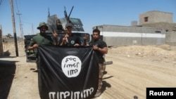 Иракские солдаты с флагом ИГ, снятым ими в городе Хит, 2 апреля 2016 года.