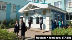 Students stand outside School No. 7 after a teenager brought a pistol and a knife to his school and allegedly held his classmates hostage, in Kazan on May 13.