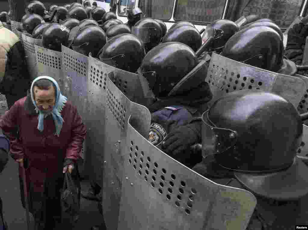 A elderly Ukrainian woman passes by security personnel as they cordon off pro-EU demonstrators near the Ministry of Internal Affairs in Kyiv on December 20. (Reuters/Gleb Garanich)