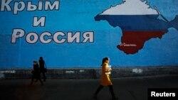Люди проходят мимо карты Крыма в цветах российского флага. 25 марта 2014 года.