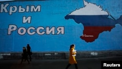 "A mural in Moscow with a map of the Ukrainian peninsula of Crimea in Russia's national colors and the words ""Crimea and Russia."""