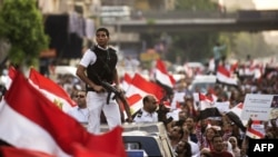 Egypt-- An armed Egyptian policeman scouts the surrounding buildings on top of a police van among protesters demonstrating with national flags against deposed President Mohammed Morsi on July 7, 2013 in Cairo, Egypt. A sea of flags fluttered wildly as ten
