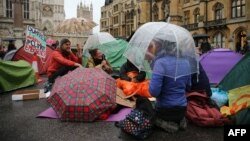 Активисты движения Extinction rebellion укрываются под зонтами от дождя во время акции протеста. Лондон, 7 октября 2019 года.