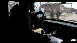 Проросійський бойовик керує автомобілем у прифронтовому населеному пункті Широкине, 20 березня 2015 року