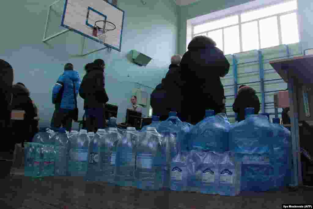 Bottled water is brought into a hall for residents following the explosion.