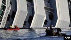 "Rescuers pass in a small boat near the stricken cruise liner ""Costa Concordia"" lying aground in front of the Isola del Giglio."