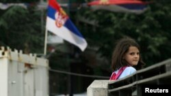 Eight-year-old Rinesa Koshi heads home past a Serbian flag as she crosses a bridge that separates the ethnically divided sections of Mitrovica, in Kosovo.