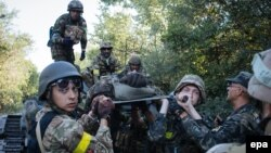 Українські військові несуть пораненого під час бою поблизу міста Іловайська, 10 серпня 2014 року