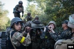 Українські військовослужбовці несуть пораненого під час боїв біля Іловайська. 10 серпня 2014 року