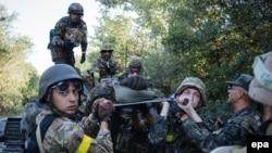 Українські військовослужбовці несуть пораненого під час бойових дій під Іловайськом, серпень 2014 року