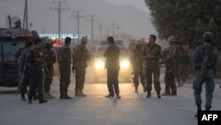 Afghan security personnel gather as they keep watch near the site of a suicide bomb attack near the Marshal Fahim military academy base in Kabul on October 21.