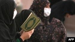Saudi Arabia -- Women Muslim pilgrims wearing flu masks pray and read the Koran in the courtyard of the Prophet Mohammed Mosque in Medina, 12Nov2009