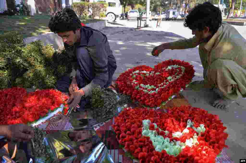 Pakistani vendors prepare heart-shaped bouquets for sale ahead of Valentine's Day along a street in Islamabad on February 13.