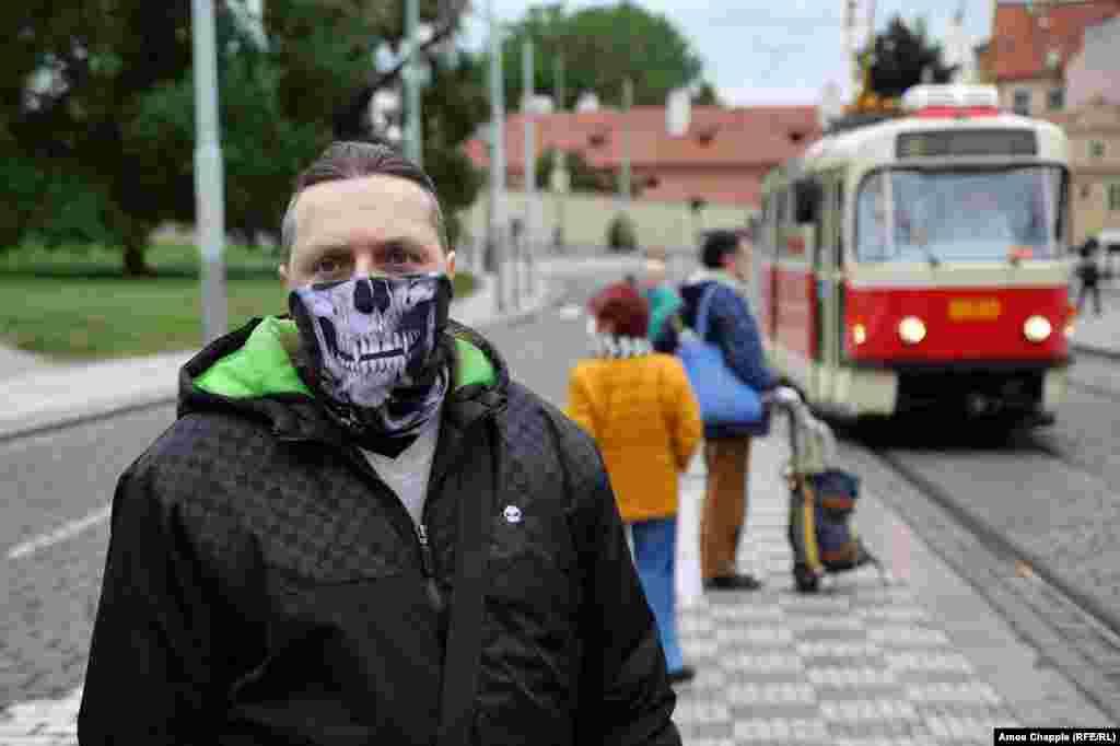 Мужчина ждет трамвай. Хотя правила, требующие ношение масок для лица в общественных местах, были резко ослаблены, люди в Чехии обязаны носить маски в общественном транспорте и во многих зданиях