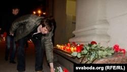 Люди возлагают цветы на Октябрьской площади в центре Минска