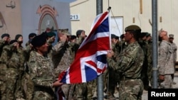 British troops lower the Union Flag during a ceremony marking the end of operations for U.S. Marines and British combat troops in Helmand Province on October 26, 2014.