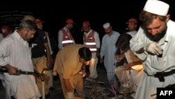 Pakistani security officials collect evidence from the site of a suicide bomb attack in Peshawar on June 11.