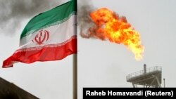 IRAN -- FILE PHOTO: A gas flare on an oil production platform in the Soroush oil fields is seen alongside an Iranian flag in the Persian Gulf, Iran, July 25, 2005.