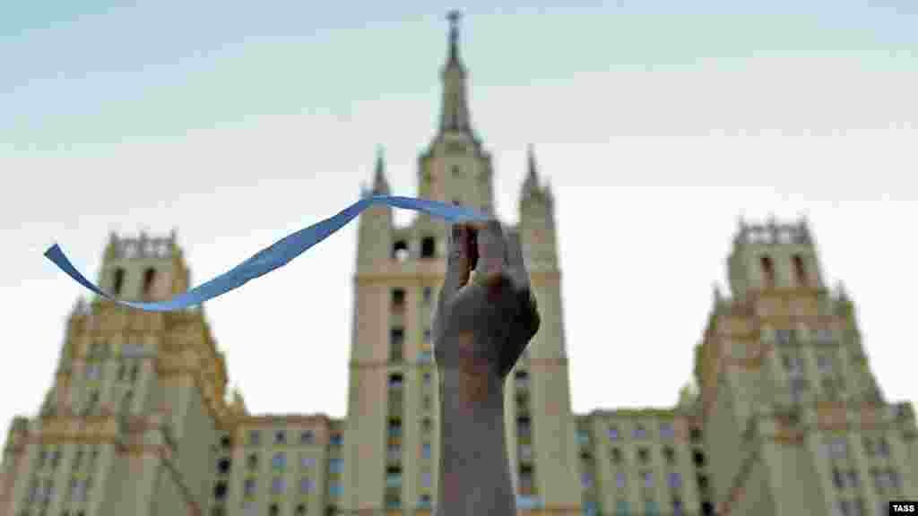 A Russian opposition activist waves a white ribbon on Kudrinskaya Square in central Moscow. (ITAR-TASS/ Sergei Karpov)