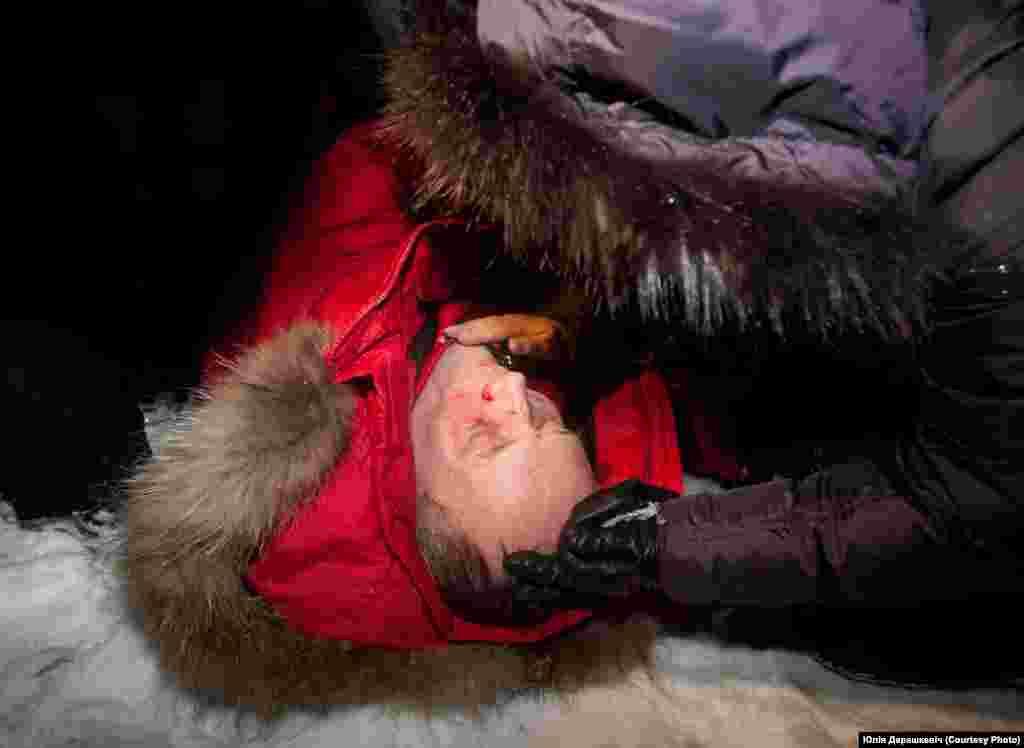 Жонка Вольга схіляецца над зьбітым кандыдатам у прэзыдэнты Ўладзімерам Някляевым. 19 сьнежня 2010 году.