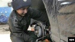 طفل عراقي يعمل في ورشة لتصليح السيارات