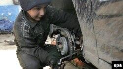 طفل عراقي يعمل في ورشة لاصلاح السيارات